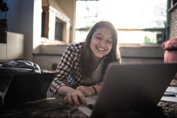 happy teen girl at laptop